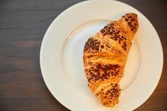 在一张陶瓷板材和洗碗布的新鲜的新月形面包 在一张黑暗的木桌上的新近地被烘烤的新月形面包 免版税库存图片