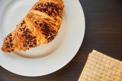 在一张陶瓷板材和洗碗布的新鲜的新月形面包 在一张黑暗的木桌上的新近地被烘烤的新月形面包 免版税图库摄影