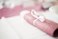 在一张餐桌安置的滚动的桃红色餐巾 库存照片