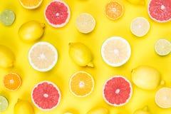 在一张黄色木桌上谎言一起切了柠檬和石灰和greyfruit 库存照片
