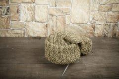 在一张黑暗的木桌上的手工制造被编织的帽子在石墙对面 库存照片
