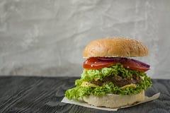 在一张黑暗的桌上的新鲜的自创汉堡 r 免版税库存照片