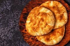 在一张黑暗的桌上的皮塔饼面包 免版税库存照片