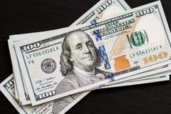 在一张黑木织地不很细桌上的新的美国一百美元票据 在视图之上 金钱和财务的概念 库存照片