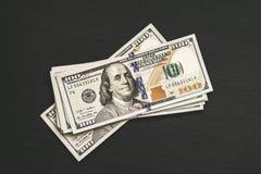 在一张黑木织地不很细桌上的新的美国一百美元票据 在视图之上 金钱和财务100的概念 库存照片