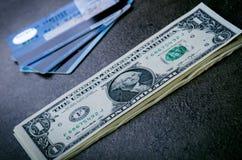 在一张黑桌上的一美元钞票与信用卡 现金金钱美国人美元 背景几何老装饰品纸张葡萄酒 透镜火光 美国杂种狗 免版税库存图片