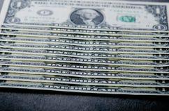 在一张黑桌上的一美元钞票 现金金钱美国人美元 背景几何老装饰品纸张葡萄酒 透镜火光 美国货币查出的四分之一白色 免版税库存照片