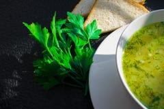 在一张黑桌上的开胃鸡汤汤用面包和荷兰芹 免版税库存照片