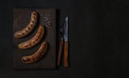 在一张黑暗的木板顶视图的烤香肠 图库摄影