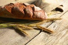 在一张黑暗的木桌上的土气有壳的面包和麦子耳朵 免版税库存照片
