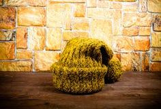 在一张黑暗的木桌上的手工制造被编织的帽子在石墙对面 免版税库存照片