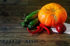在一张黑暗的桌上的新鲜蔬菜 秋天背景特写镜头上色常春藤叶子橙红 吃健康 南瓜,甜椒,辣椒粉,蕃茄,玉米棒子 免版税库存照片