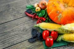 在一张黑暗的桌上的新鲜蔬菜 秋天背景特写镜头上色常春藤叶子橙红 吃健康 南瓜,甜椒,辣椒粉,蕃茄,蓬蒿 库存图片