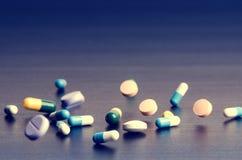 在一张黑暗的桌上的药房背景 升空药片 在倒下黑暗的背景的片剂  药片 医学和健康 免版税库存图片