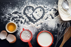 在一张黑暗,石桌上的烘烤成份:鸡蛋、面粉和牛奶 图库摄影