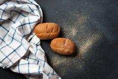 在一张黑桌上的两个新鲜的麦子小圆面包,在一块蓝色和白色亚麻制毛巾 免版税库存图片