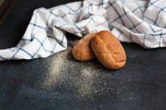 在一张黑桌上的两个新鲜的麦子小圆面包,在一块蓝色和白色亚麻制毛巾 免版税库存照片