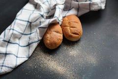在一张黑桌上的两个新鲜的麦子小圆面包 库存图片