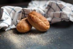在一张黑桌上的两个新鲜的麦子小圆面包 库存照片