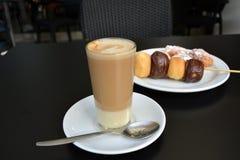 在一张黑桌上的杯可口泡沫似的coffe和点心 图库摄影