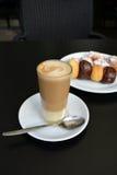 在一张黑桌上的杯可口泡沫似的coffe和点心 免版税库存照片