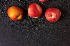 在一张黑桌上的桃子在下落 库存图片
