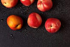 在一张黑桌上的桃子在下落 免版税库存照片