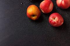 在一张黑桌上的桃子在下落 免版税库存图片