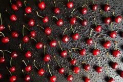 在一张黑桌上的甜樱桃背景 水滴莓果的表面上的 在视图之上 平的位置 免版税库存照片