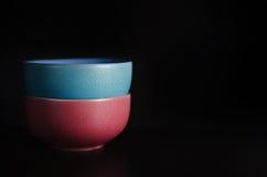 在一张黑桌上的红色和蓝色碗 图库摄影