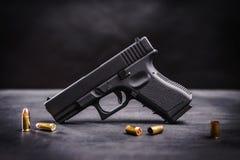 在一张黑桌上的黑手枪 库存图片