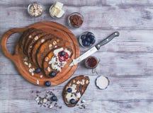在一张轻的木桌上切了面包用果子和坚果 免版税图库摄影