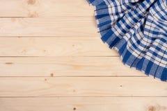 在一张轻的木桌上的蓝色方格的桌布与您的文本的拷贝空间 顶视图 库存图片