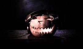 在一张dj桌上的万圣夜南瓜与在黑暗的背景的耳机与拷贝空间 愉快的万圣夜节日装饰和音乐 库存图片