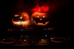 在一张dj桌上的万圣夜南瓜与在黑暗的背景的耳机与拷贝空间 愉快的万圣夜节日装饰和音乐 库存照片