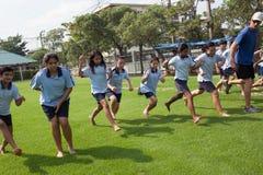 在一所学院在曼谷,在户外运动期间的小学生 免版税库存照片