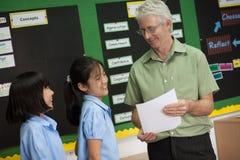 在一所学院在曼谷,学校教师改正了并且帮助他的工作的一名学生 图库摄影