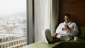 在一手机和微笑的年轻人微笑的英俊的人佩带的浴巾传讯 他在窗口附近坐与 股票录像
