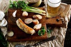 在一把切板的烤自创香肠肉馅、葱、大蒜、腌汁和啤酒、叉子和刀子在纸 库存照片
