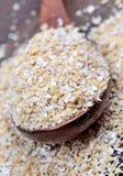 在一把匙子的燕麦在木背景 库存照片
