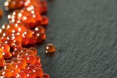 在一把匙子的红色鱼子酱在黑板岩背景 免版税库存图片