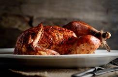 在一把卵形盛肉盘、葡萄酒刀子和叉子的烤鸡在黑暗的背景的一块餐巾 免版税库存图片