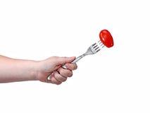在一把叉子的红色蕃茄在白色backgrou隔绝的一只女性手上 免版税库存照片