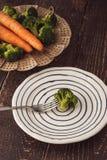 在一把叉子的蒸的硬花甘蓝在木桌上的陶瓷板材 库存图片