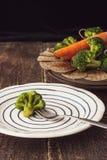 在一把叉子的蒸的硬花甘蓝在陶瓷板材垂直 免版税库存图片
