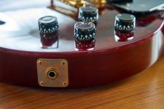 在一把发光的葡萄酒红吉他的输入杰克有金黄硬件地方的 免版税库存照片