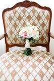 在一把古色古香的扶手椅子的婚礼花束 库存照片