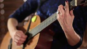 在一把声学吉他的串的手 特写镜头 一件蓝色礼服的一个女孩弹奏一个乐器 在开始的Defocus 影视素材