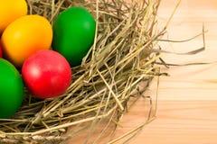 在一把干草的干草的复活节彩蛋在一张木桌上的 免版税库存图片