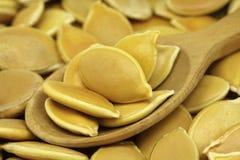 在一把木匙子的几粒南瓜籽 免版税图库摄影
